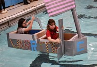 two students competing in cardboard boat races