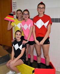 four students standing with their cardboard boat