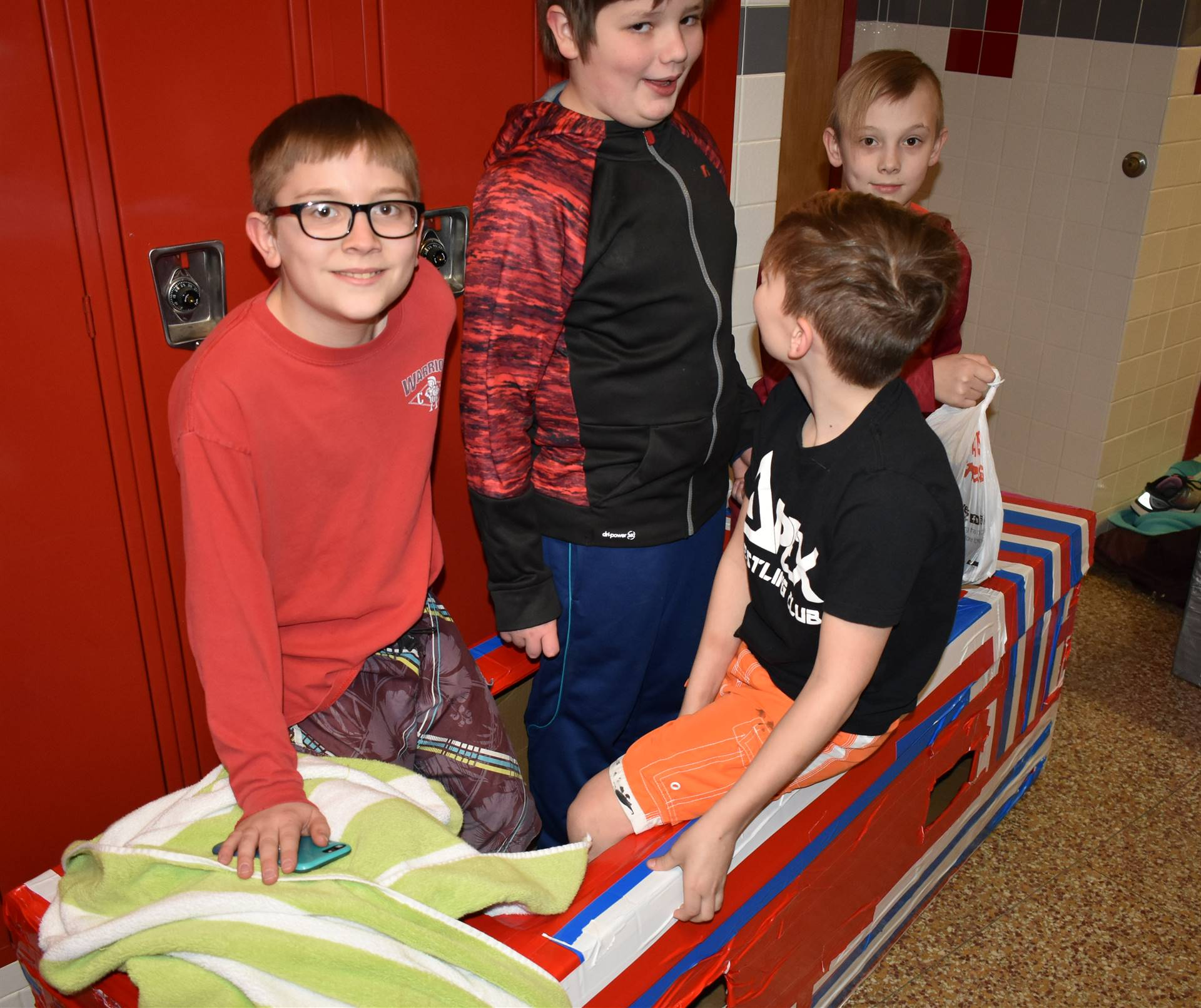 four students sitting in their cardboard boat