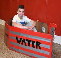 student sitting in cardboard boat