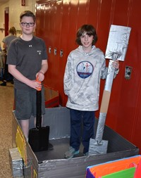 two students standing with their cardboard boat