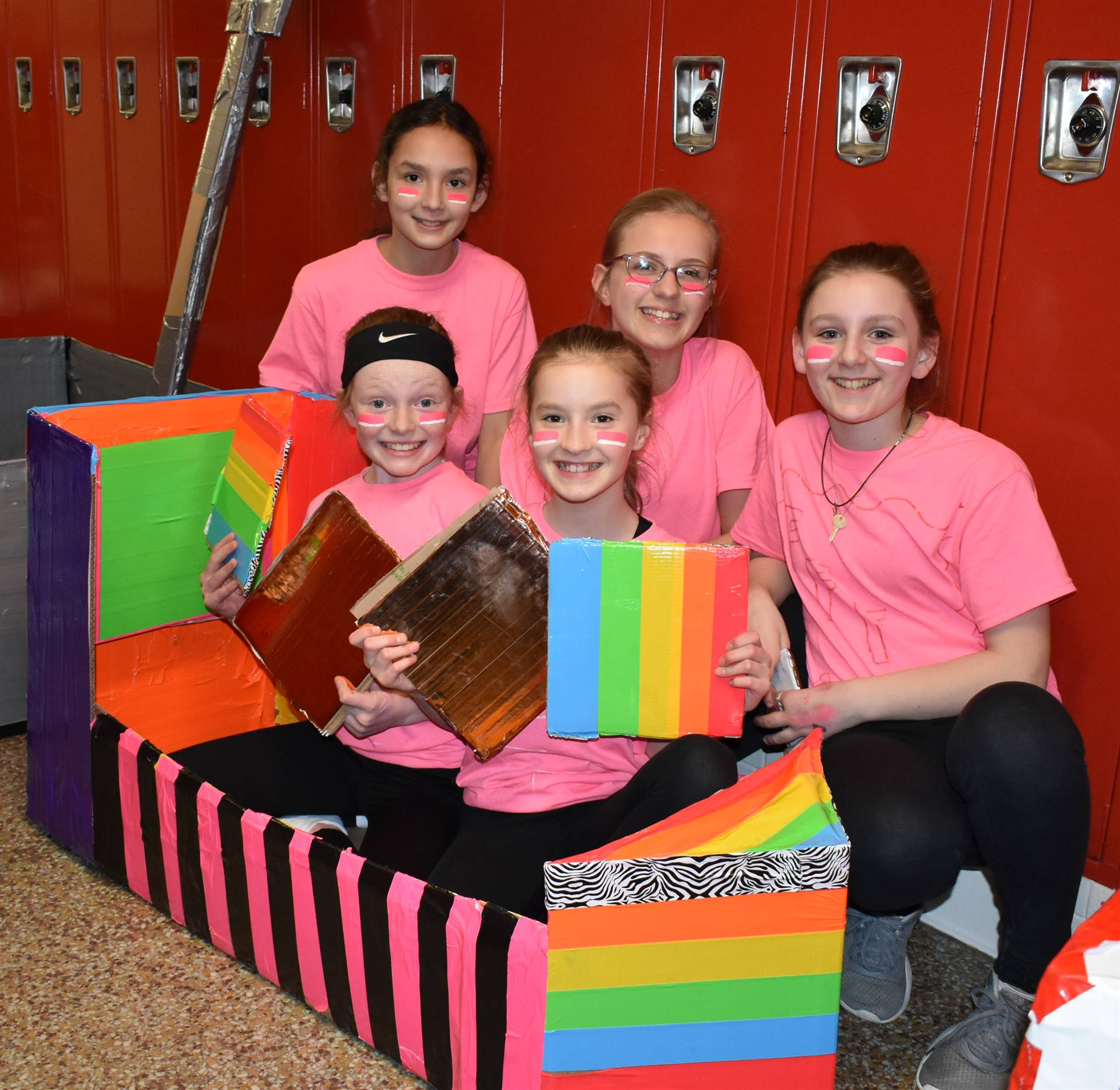 five students sitting with their cardboard boat