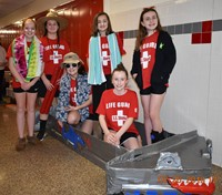six students standing with their cardboard boat