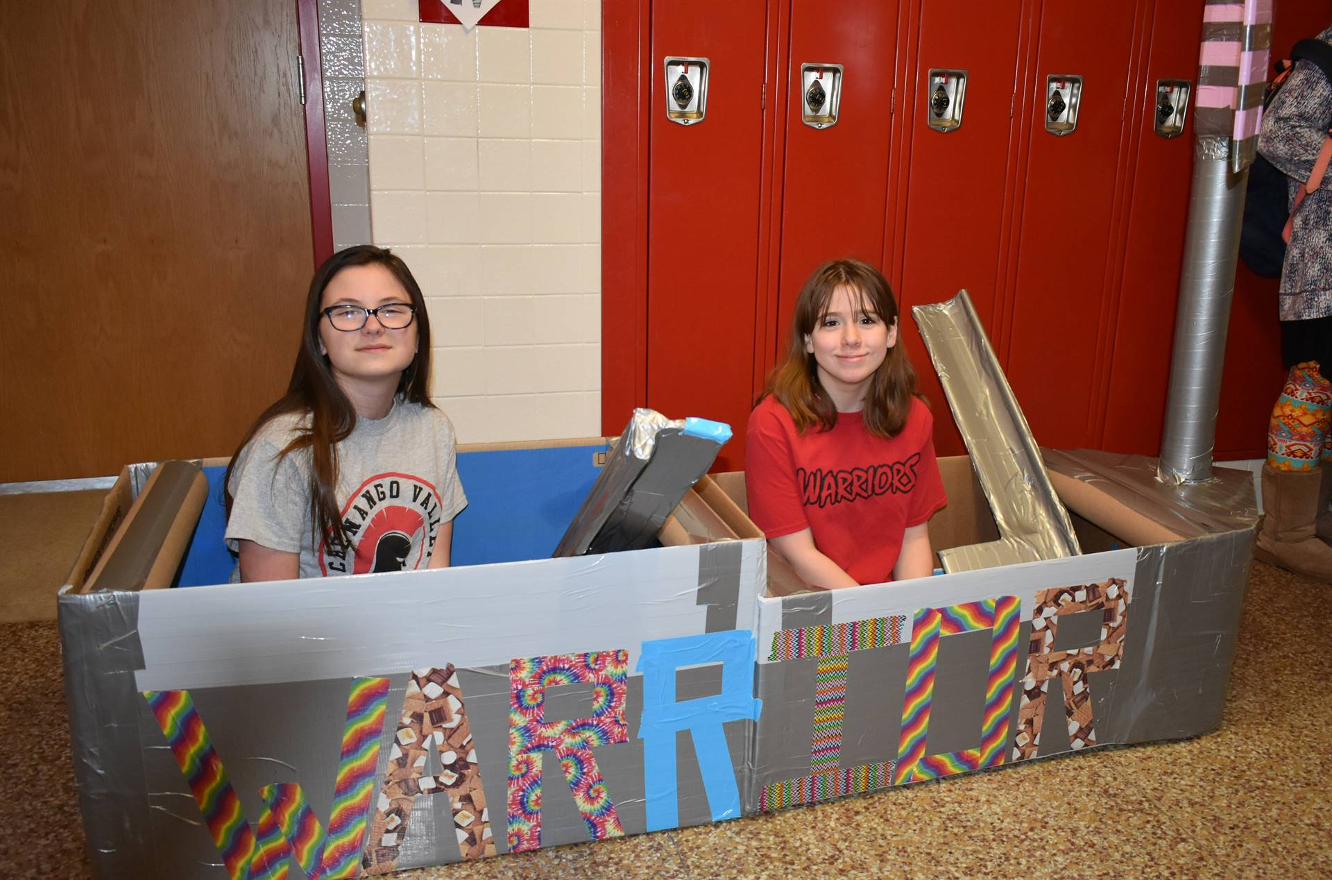 two students sitting in their cardboard boat