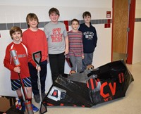 five students standing with their cardboard boat