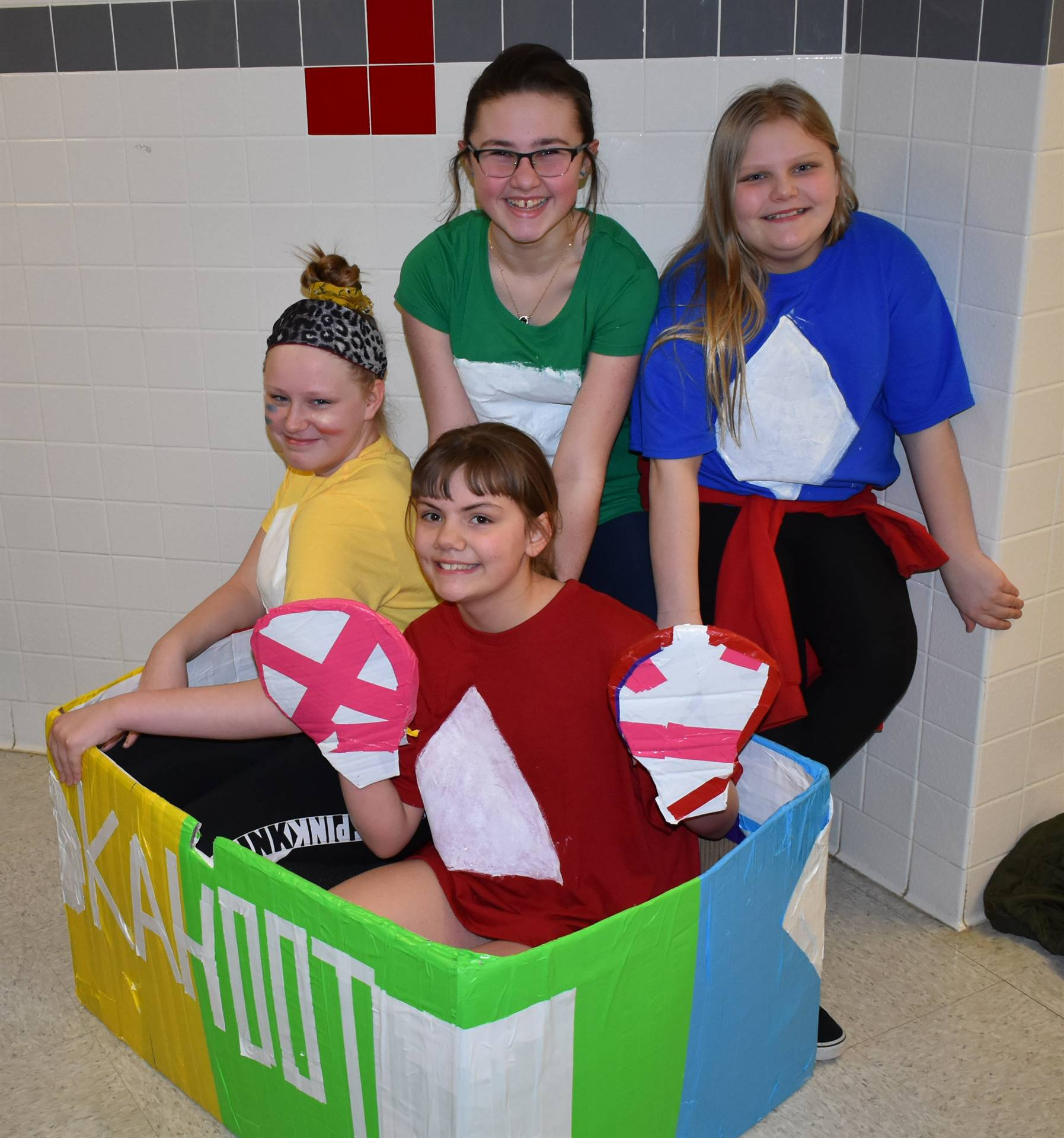 four students with their cardboard boat