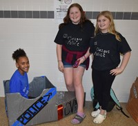 three students with their cardboard boat