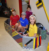 three students sitting in their cardboard boat