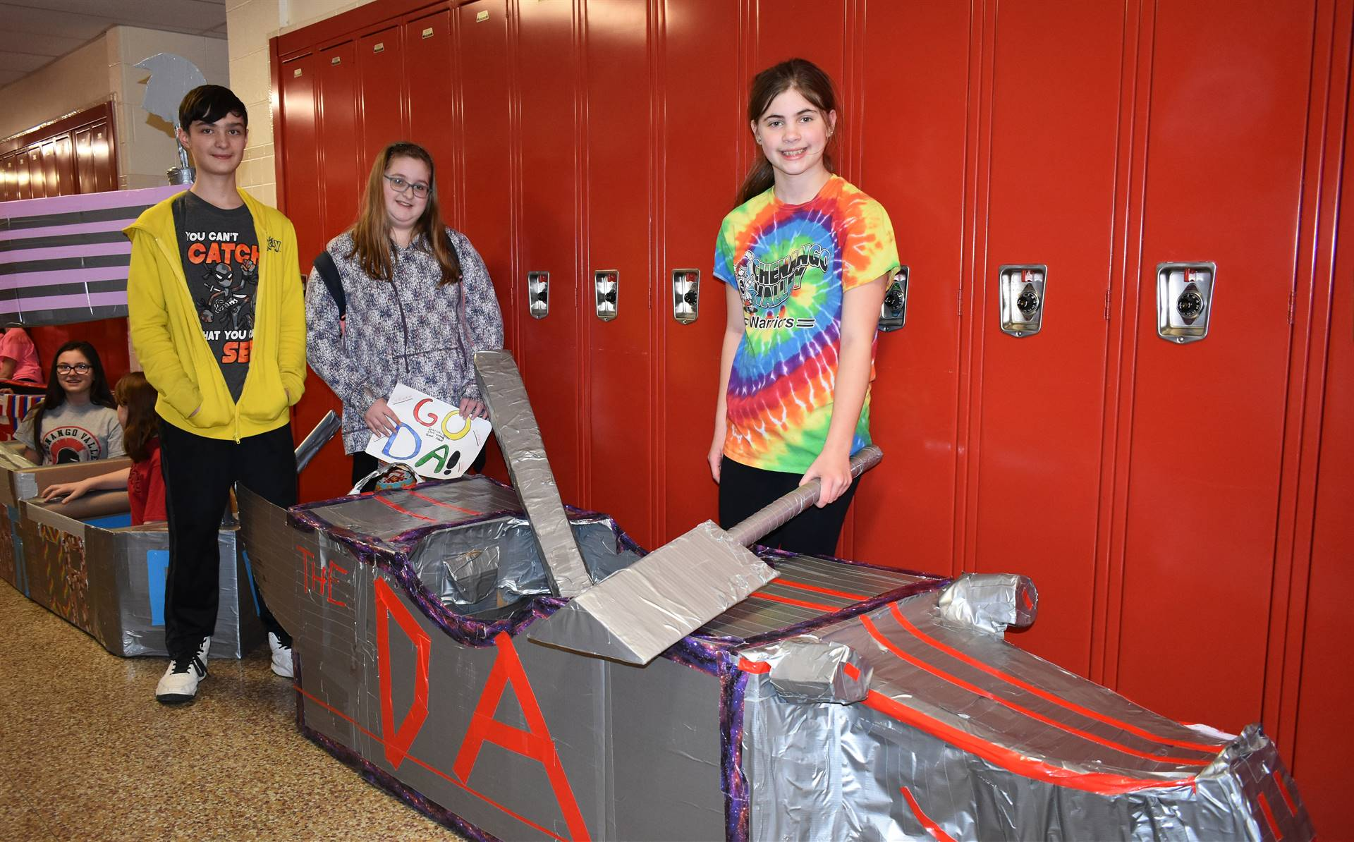three students standing with their cardboard boat