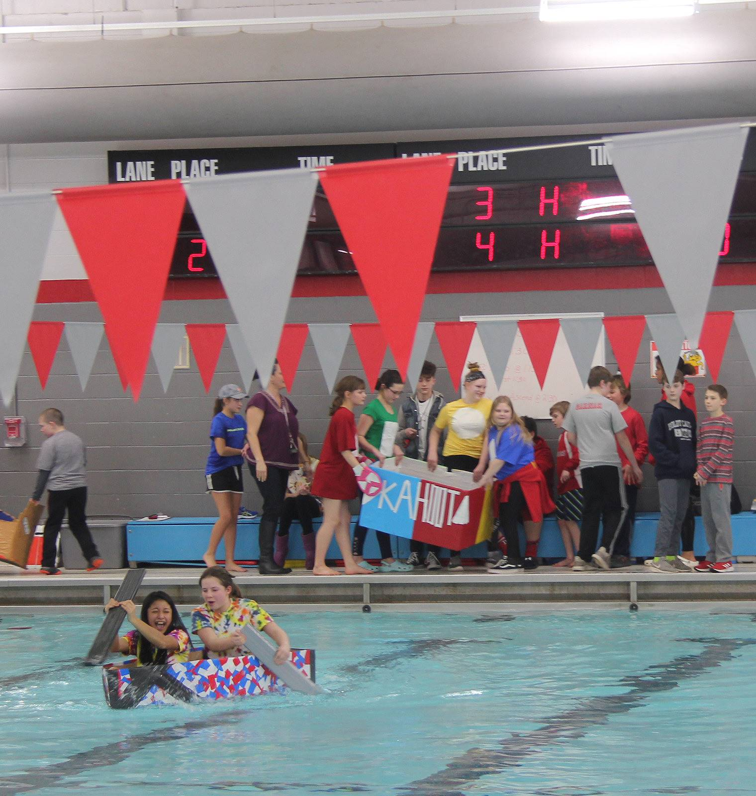 wide shot of two students competing in cardboard boat race