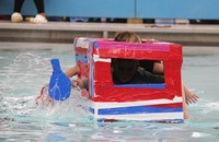 two students competing in cardboard boat race
