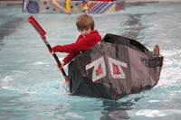 student competing in cardboard boat race