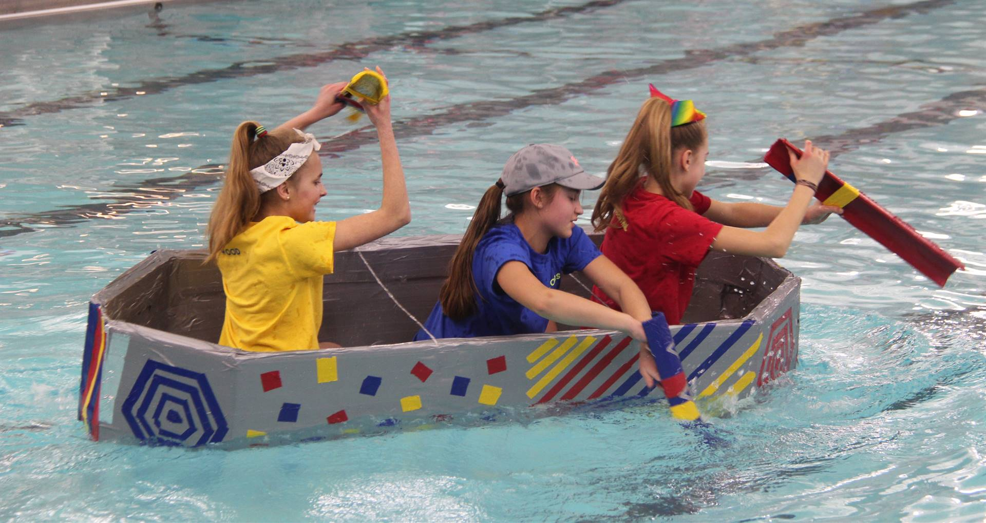 three students competing in cardboard boat race