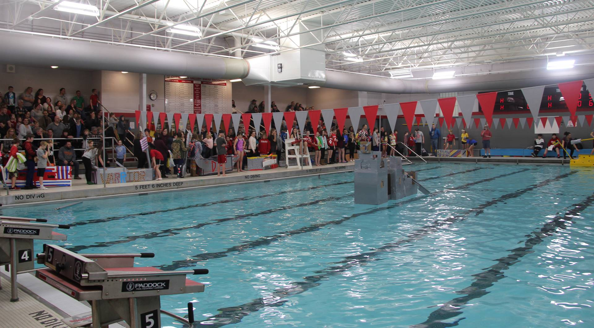 wide shot of students competing in cardboard boat race