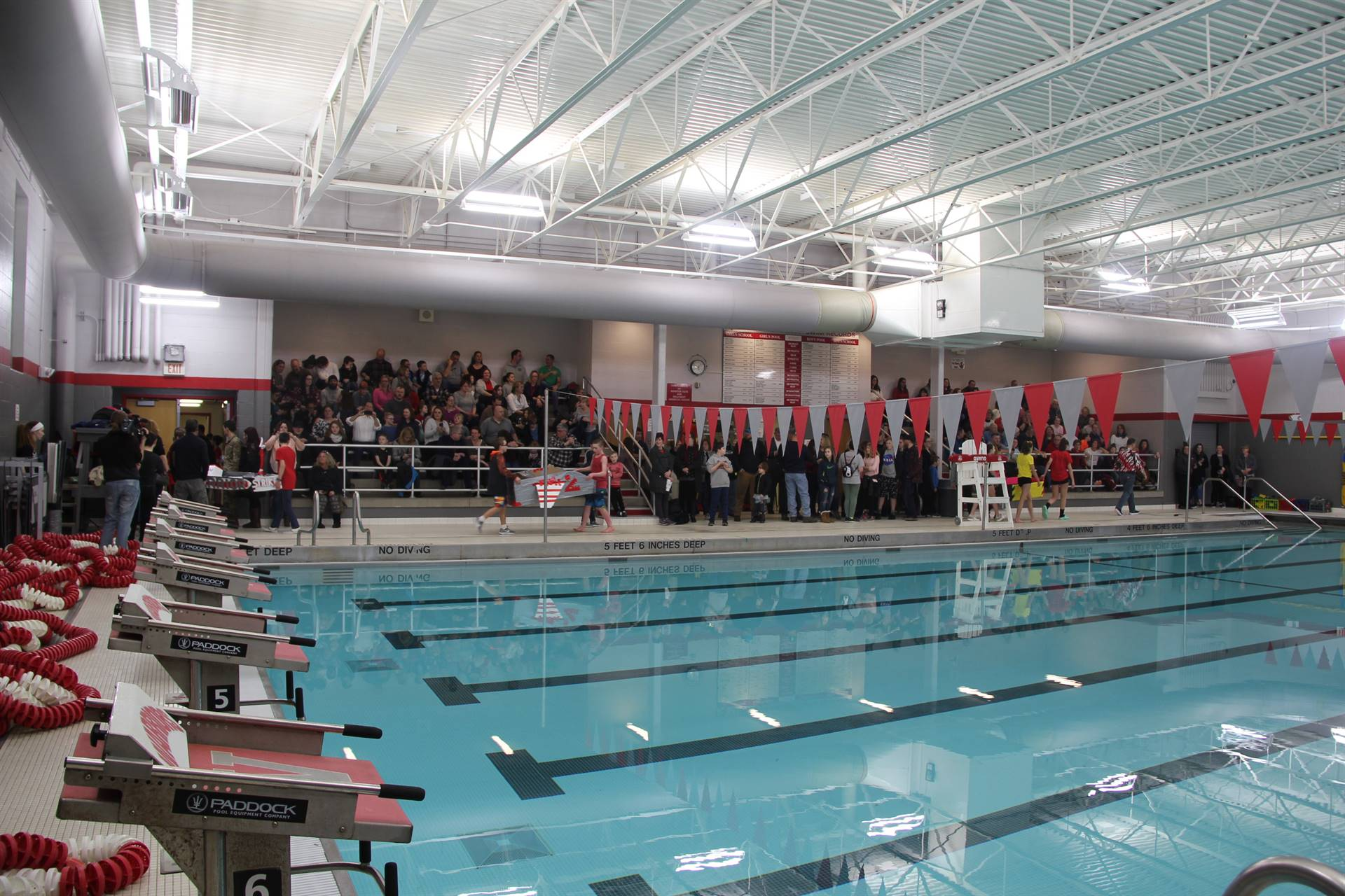 students of students entering pool area for cardboard boat races