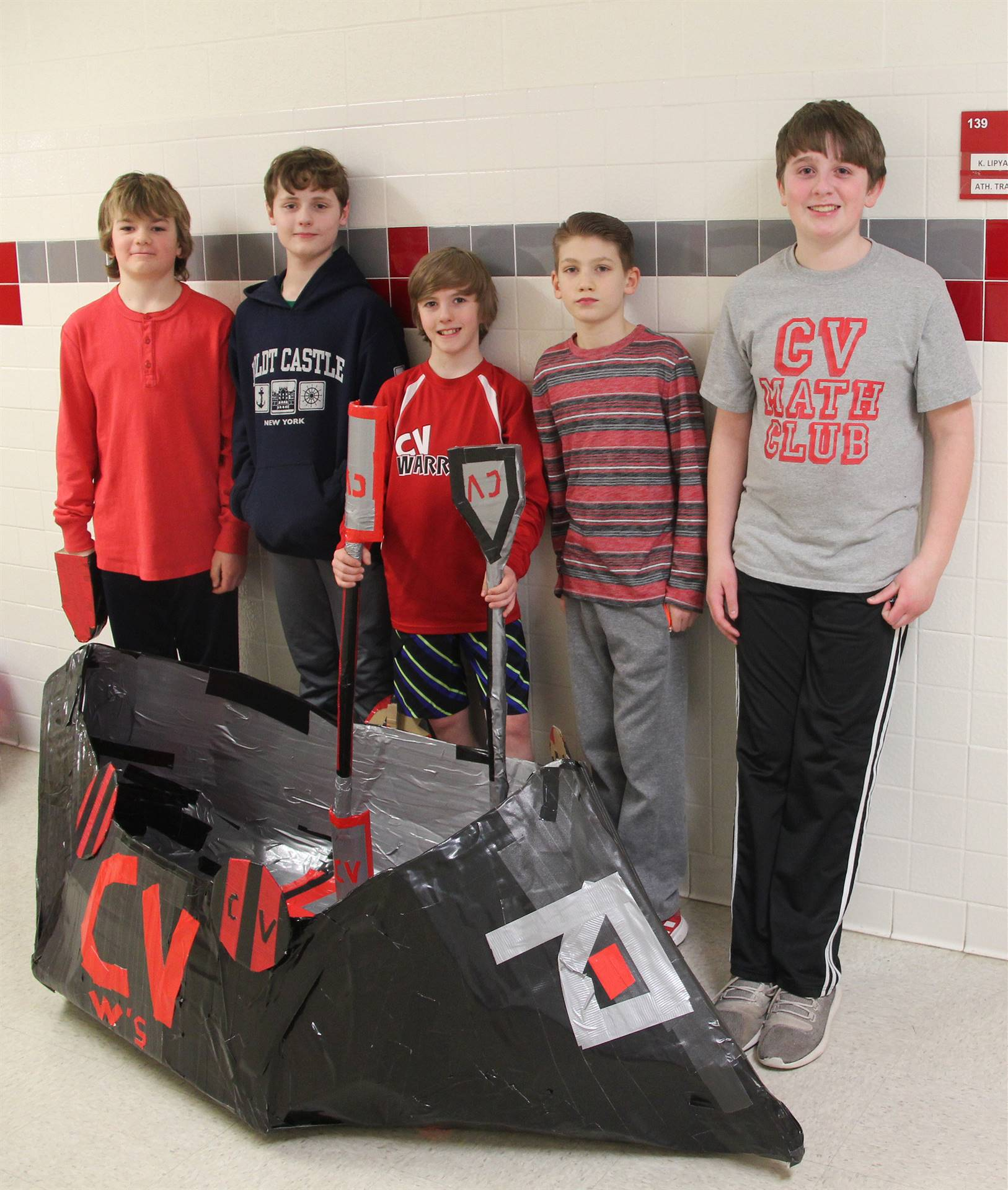 five students standing with cardboard boat