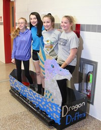 four students standing with cardboard boat
