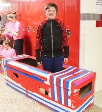 student standing with cardboard boat