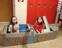 two students sitting in cardboard boat