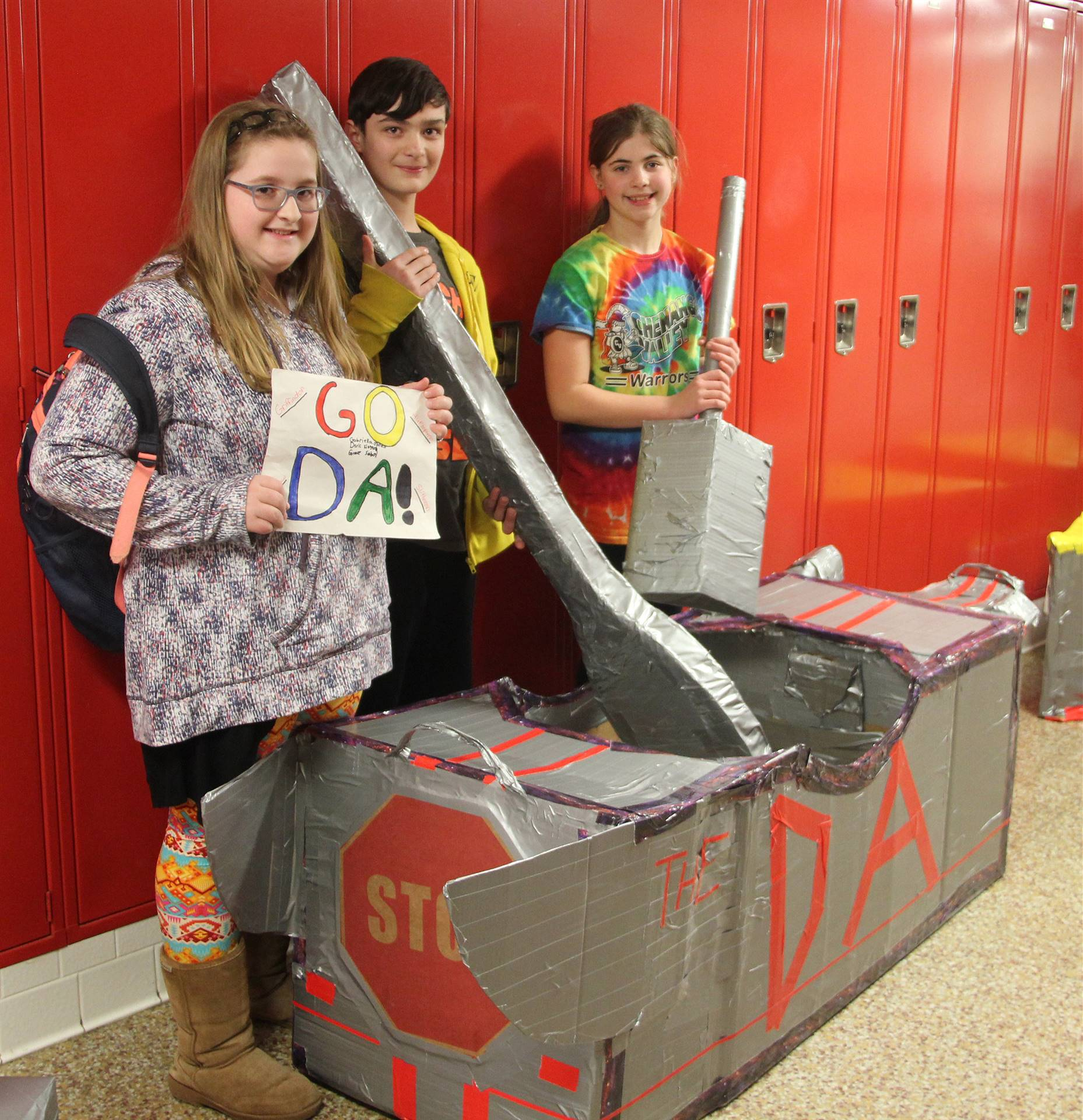 three students standing with cardboard boat