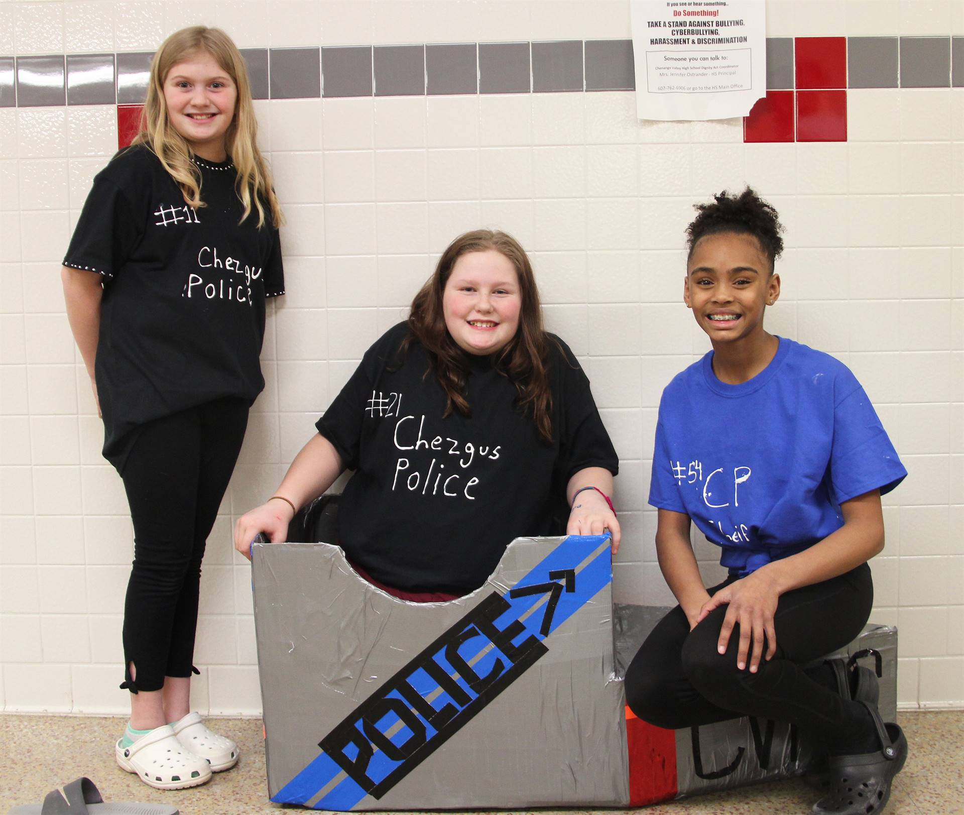 three students with cardboard boat