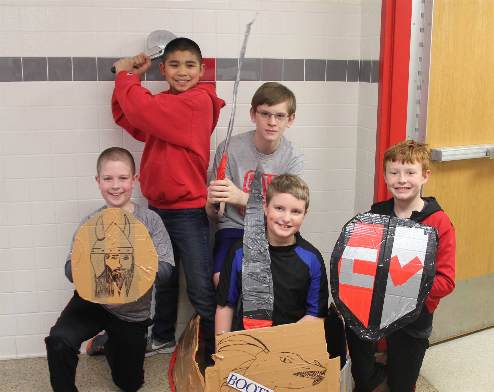 five students with cardboard boat