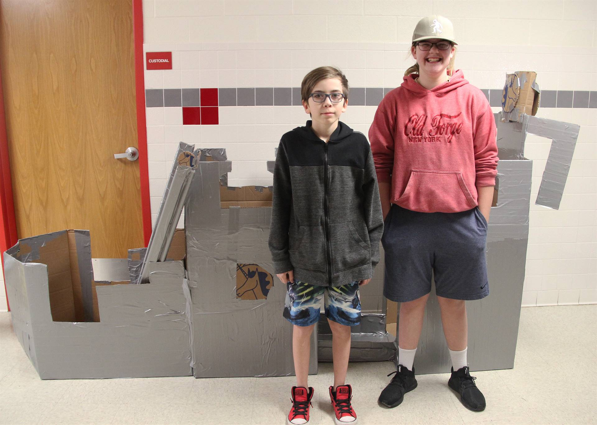 two students standing with cardboard boat