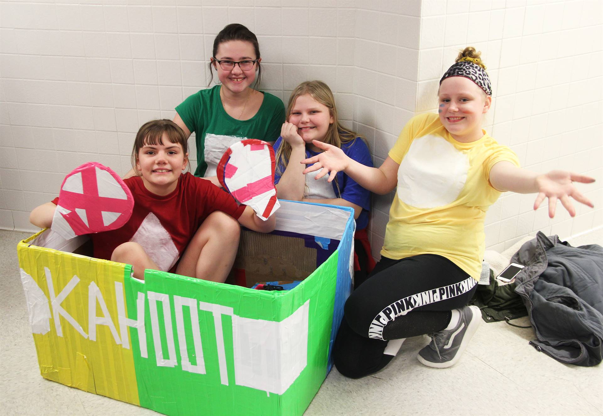 four students with cardboard boat