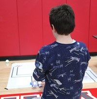 student taking part in steam night activity involving robots