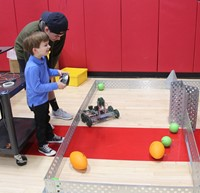 high school student helping younger student with robotics activity