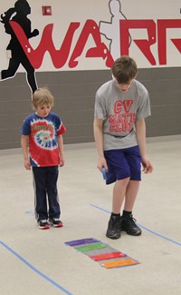 middle school student showing younger student how to complete activity