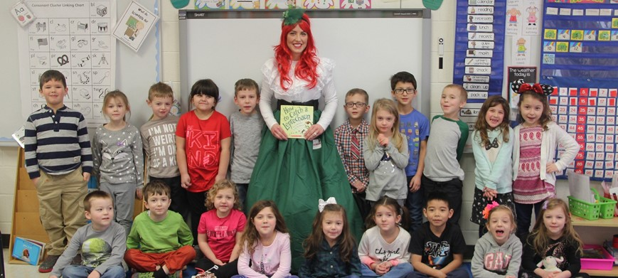 students with leprechaun lady and p t a book donation