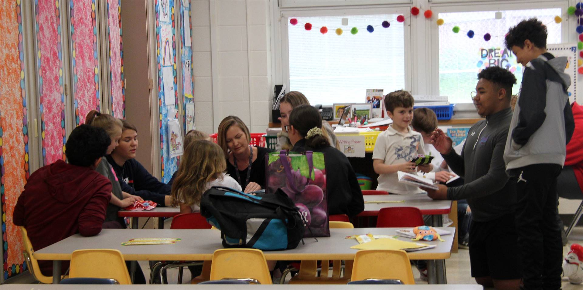 high school and middle school students reading to kindergarten students 8