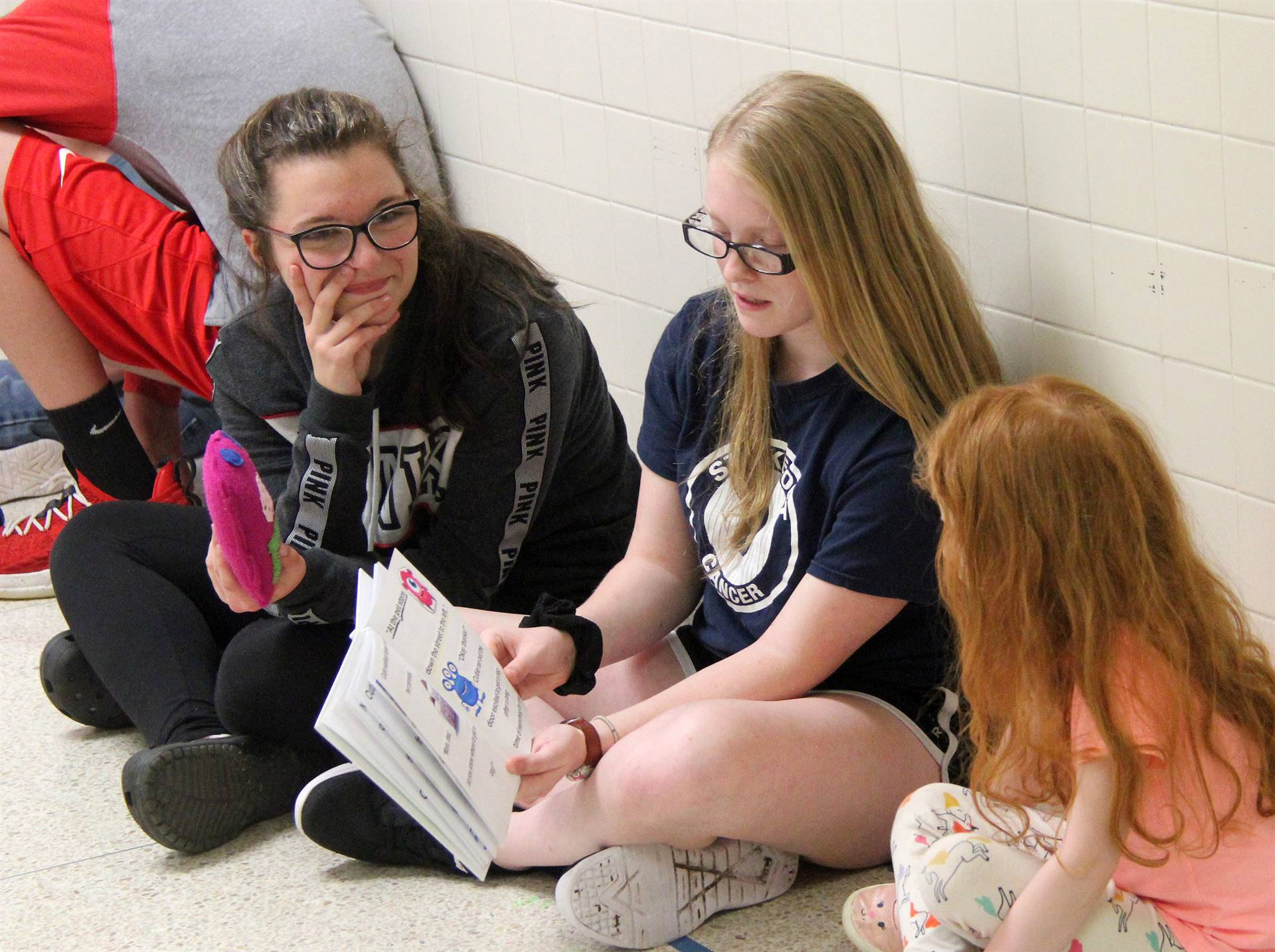 high school and middle school students reading to kindergarten students 3
