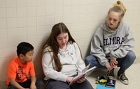 high school and middle school students reading to kindergarten students 1