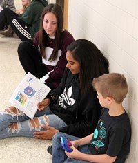 high school and middle school students reading to kindergarten students 6