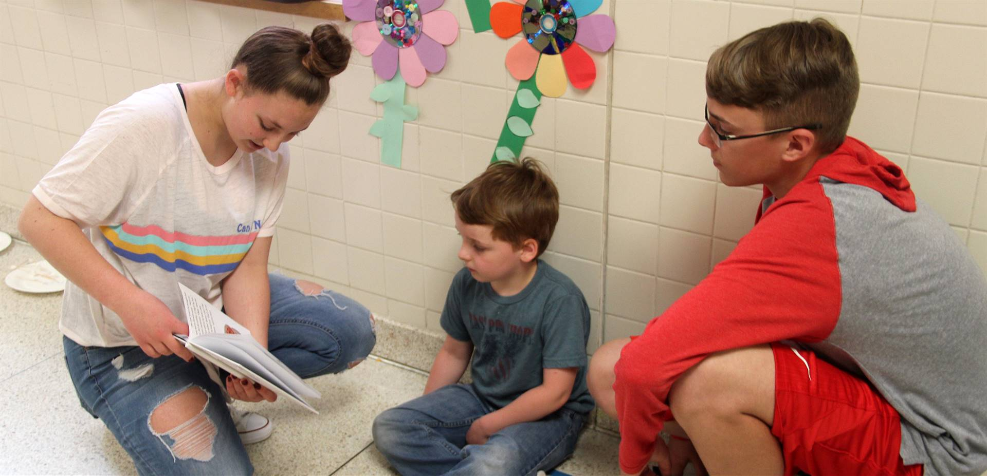 high school and middle school students reading to kindergarten students 5