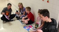 high school and middle school students reading to kindergarten students 4