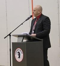 mister tomm speaking at podium