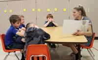 high school student reading to kindergarten students 17