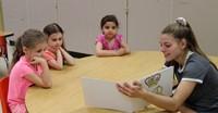 high school student reading to kindergarten students 16