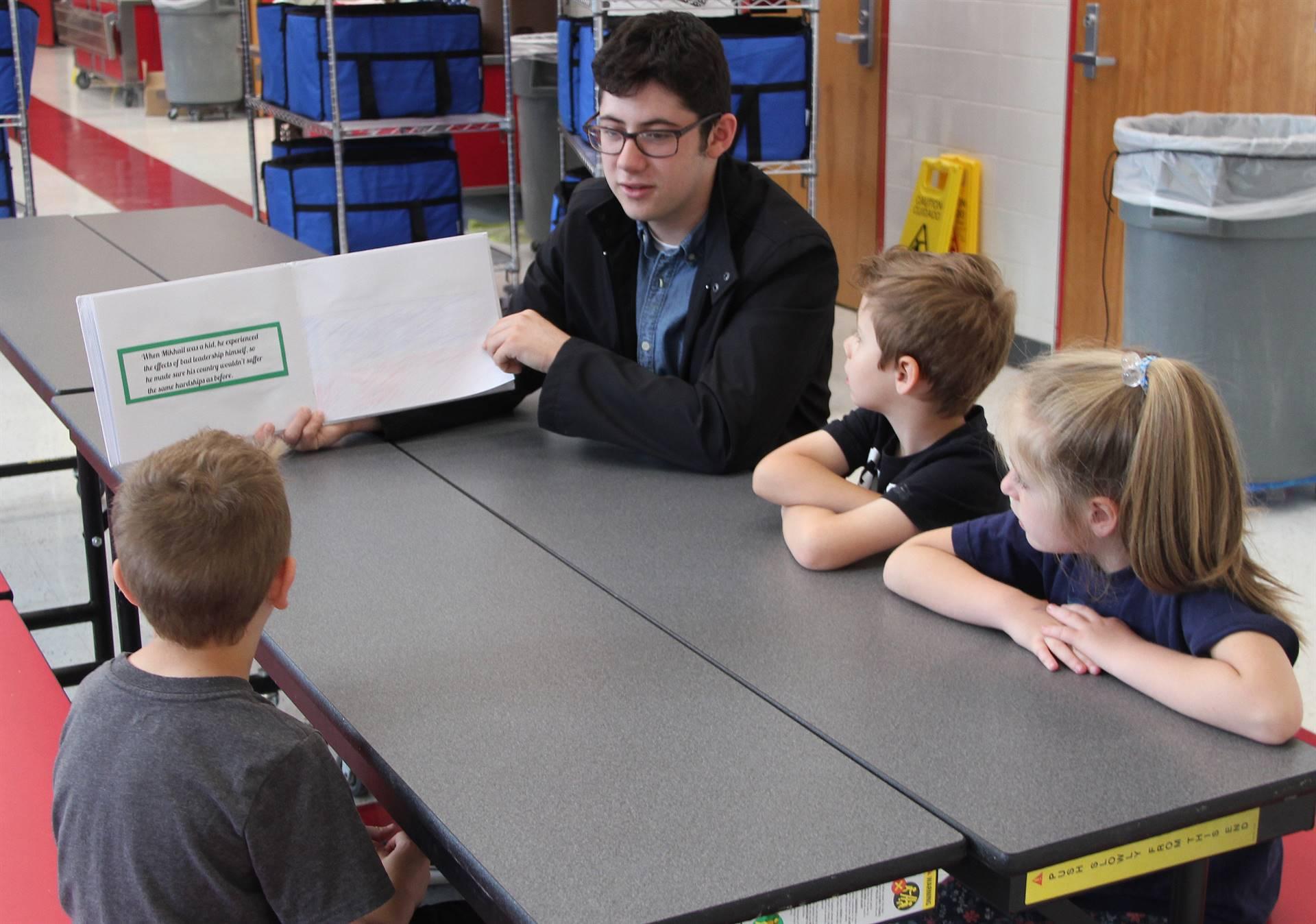 high school student reading to kindergarten students 15