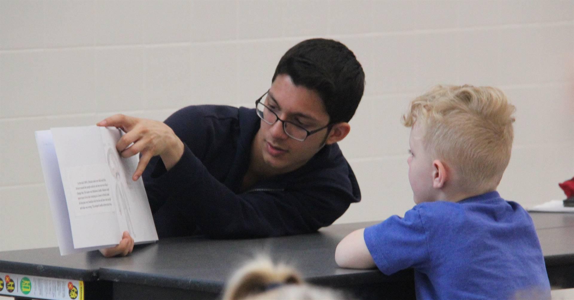 high school student reading to kindergarten students 21