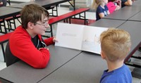 high school student reading to kindergarten student 12