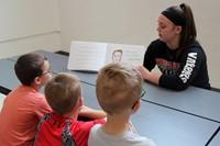 high school student reading to kindergarten students 10