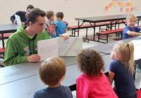 high school student reading to kindergarten students 9