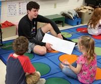 high school student reading to kindergarten students 7
