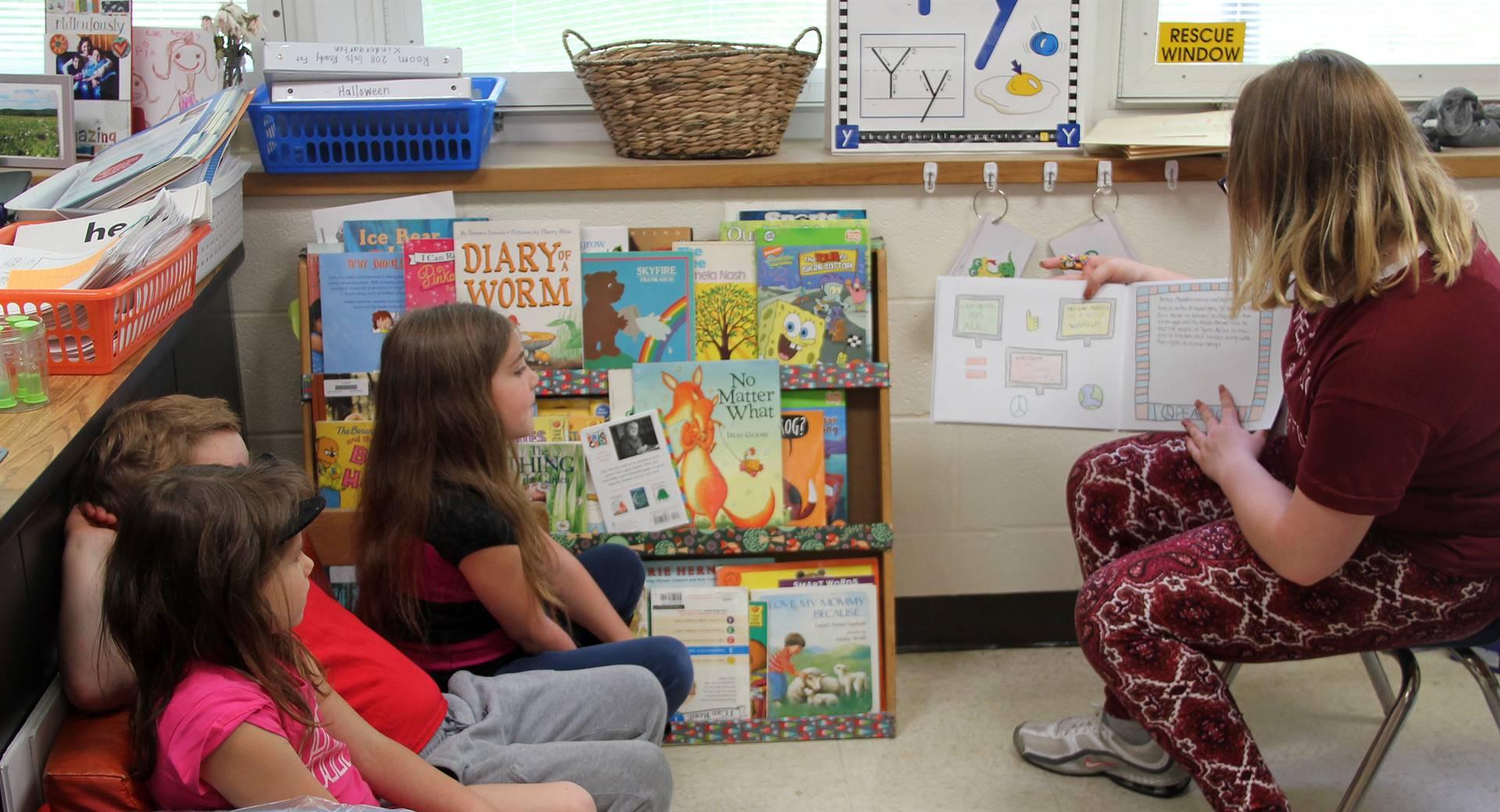 high school student reading to kindergarten students 6