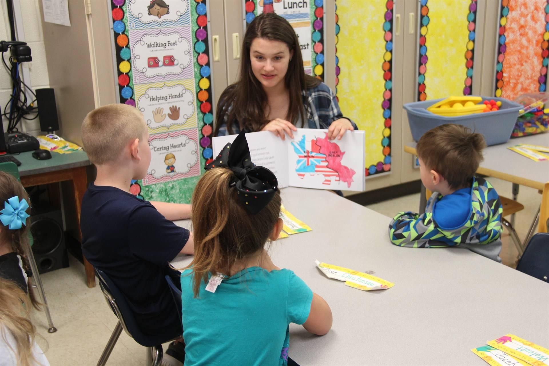 high school student reading to kindergarten students 4