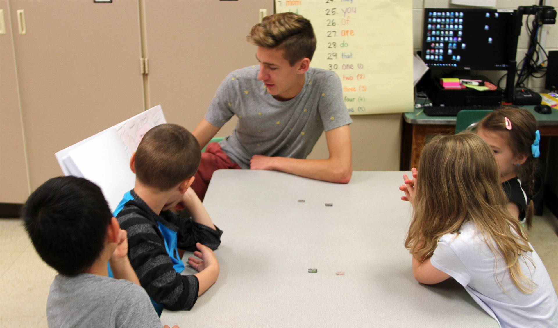 high school student reading to kindergarten students 3